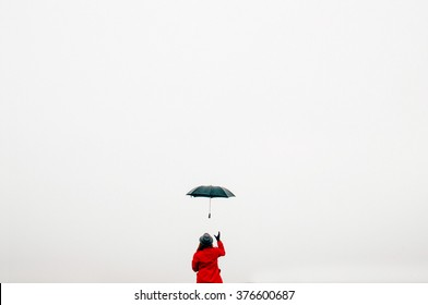 Girl in a hat and a red raincoat throws up a black umbrella on whine backgraund. Umbrella woman jump. Girl throws up an umbrella in the sky. VSCO