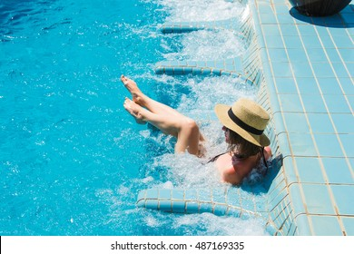 Girl in hat relaxing in spa swimming pool and jacuzzi, enjoying vacation. Luxury lifestyle, healthy legs, skin care concept.Dream life. Summer fashion. Glamorous beauty. Time to travel. Rich people