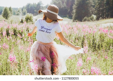 The girl in the hat runs across the field with her hands to the sides, the skirt fluttering in the wind.