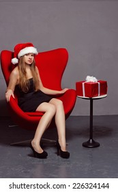 girl in the hat of Santa Claus on Christmas gifts near