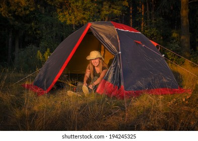 girl in hat sits inside the camp tent