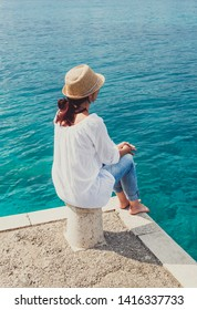 Girl with a hat is sitting on a mole and looking at the sea