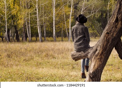 Girl in a hat sitting on a tree in the autumn forest. Back view.