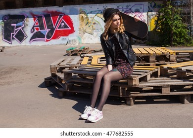 Girl in a hat sitting with the skateboard on her shoulder