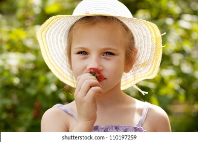 Girl in the hat smells ripe fresh strawberries