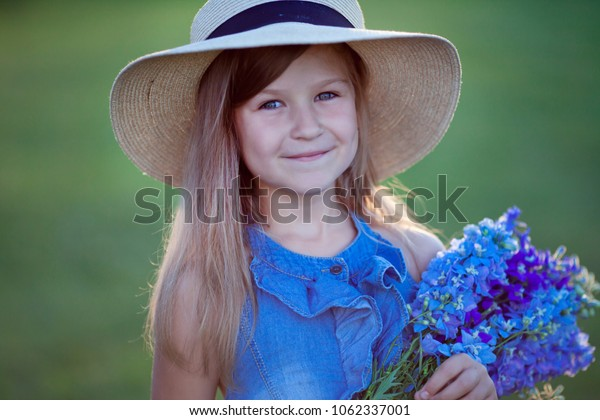 A girl in a hat smiles