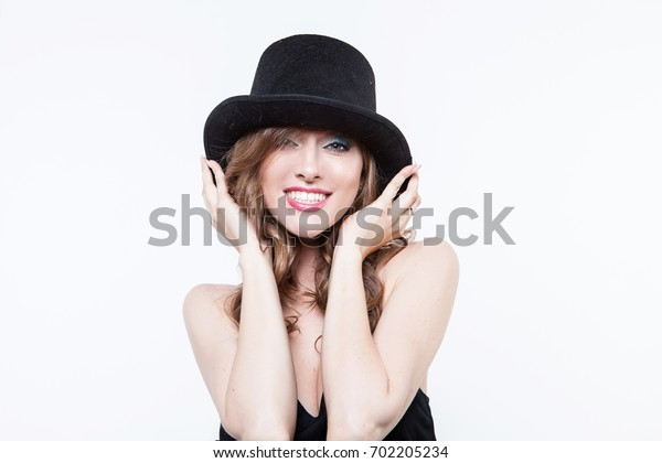 A girl in a hat smiles. Cheerful girl in cap making faces on camera on white.  Indoor portrait of a young beautiful fashionable woman.  Female fashion, beauty and advertisement concept. Close up.
