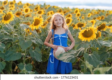 Girl with a hat stands in a field of sunflowers