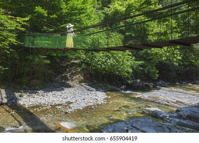 The girl in a hat strolls along a suspension bridge over a stormy mountain river in the thickets of the jungle