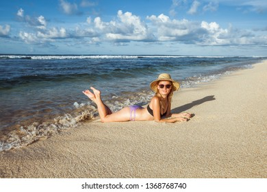 Girl in a hat and sunglasses lying on a sandy beach