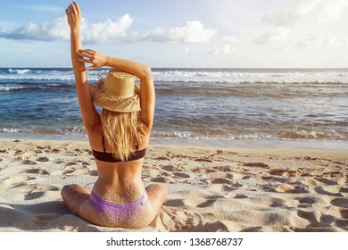 The girl in the hat and swimsuit sitting on the beach with his back to the camera and stretches his hands up. Copy space