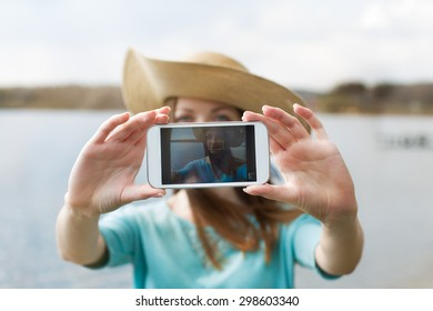 Girl in hat taking her photo on the phone