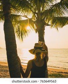 girl in a hat and tropical sunset on the ocean and palm trees