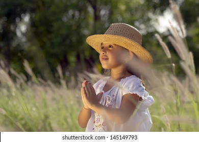 Girl with hat and white blouse has its hands in prayer position
