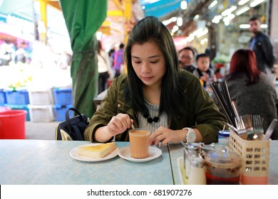 girl have breakfast in the cafe in chinese asian wet market