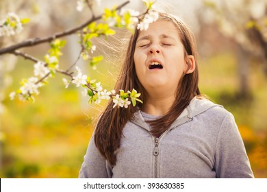 Girl having allergy outdoor, sneezing. Selective focus