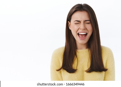 Girl having breakdown from too much stress, feel upset and uneasy screaming out loud with closed eyes, whining want someone pity her, standing lonely and sad over white background