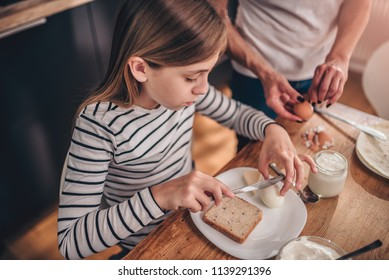 Girl having breakfast at home while her mother standing beside her and peeling boiled eggs