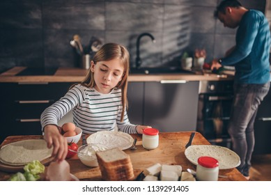 Girl having breakfast at home while her father preparing food on kitchen countertop
