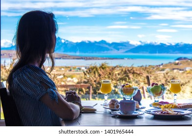 Girl having breakfast at a restaurant with mountain view