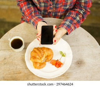 Girl having breakfast and using cell phone