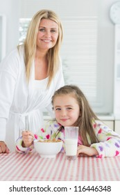 Girl having cereal for breakfast with mother in kitchen