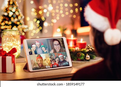 Girl having a Christmas video call with her happy family. Concept of families in quarantine during Christmas because of the coronavirus. Xmas still life with a tablet in a cozy room