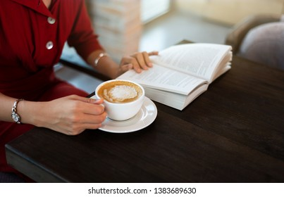 Girl having coffee in the bar and reading a book