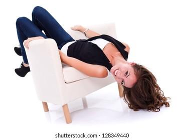 Girl having fun in the armchair, studio shot