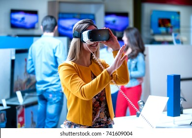 Girl having fun trying new 360 vr headset at tech store