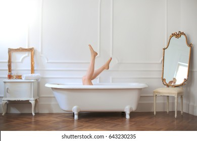 Girl having fun in the tub. She is in a spacious and elegant bathroom.