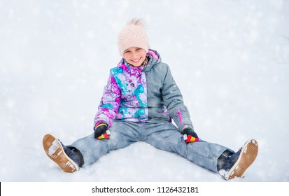 Girl having fun while sitting on the snow