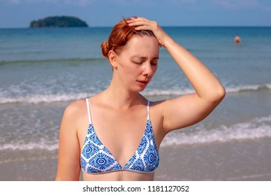 Girl having headache on seaside. Suffering woman on sunny beach. Woman sunstroke by sea. Hot sun danger. Health problem on holiday. Medicine on vacation. Dangerous sun. Medical insurance in travel