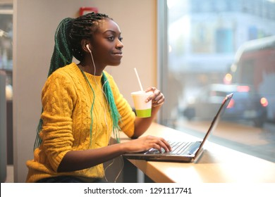 Girl having lunch in a bar, listening music and using her laptop