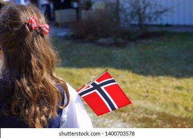 A girl having Norwegian national flag as her hair decoration and holding a national flag to celebrate the national day on the 17 of may