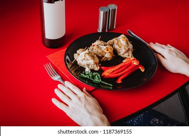 The girl is having supper at a red table with a meat dish and a bottle of wine. Serving dinner