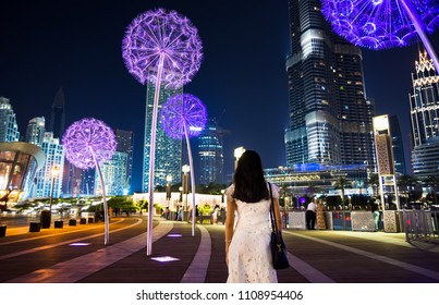 Girl having a walk in downtown Dubai at night