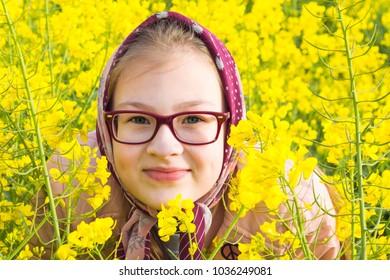 girl in  headdress against  background of  rapeseed field, protection against spring ticks