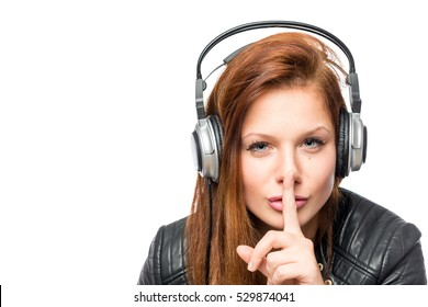 girl in headphones asks keep quiet on a white background isolated