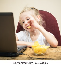 Girl with headphones eating potato chips and candy. The child spends time at the computer.