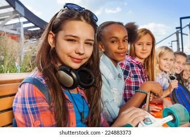 Girl with headphones and friends sit  together