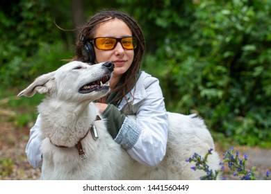 Girl in headphones and glasses hugs a dog. Latino girl of appearance with dreadlocks wearing a white windbreaker. Summer day. The joy and pleasure of communicating with animals.
