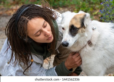 Girl in headphones and glasses hugs a dog. Latino girl of appearance with dreadlocks wearing a white jacket. Summer day. The joy and pleasure of communicating with animals.