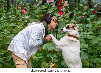 The girl in the headphones and glasses next to the dog pooch on the background of flowers. Latino girl of appearance with dreadlocks wearing a white jacket. Communication with the animal.