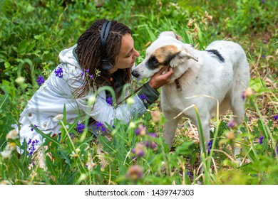 Girl in headphones hugs a dog. Latino girl of appearance with dreadlocks wearing a white windbreaker. Summer day. The joy and pleasure of communicating with animals.