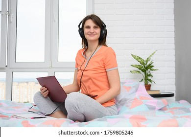 Girl in headphones and with a laptop sits at home in bed, dressed in pajamas