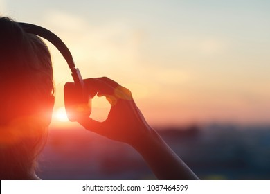 Girl in headphones listening to music in the city at sunset