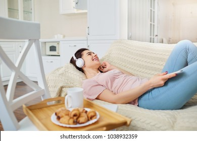 The girl in the headphones  listening to music inside the room.
