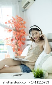 Girl with headphones listening to the music in a laptop on the bed at home