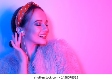 Girl in headphones listening to music. The girl smiles and laughs. Fashion portrait of young elegant girl in a pink coat and headband. Leopard print accessories. Girl dancing. Copy space for text